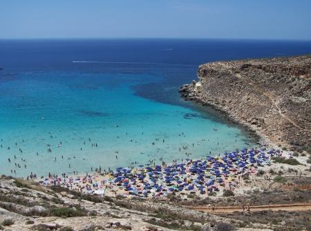 This is the magnificent island of rabbits, in Lampedusa. The water is crystal clear and the sand is white. The rocks are silhouetted against the blue sea and the sky is clear. The depths of this island are a paradise for divers because they are full of co