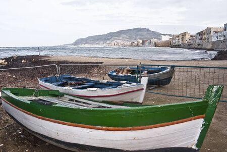 Boats in the marina of trapani with old buildings and sky cloudy photo