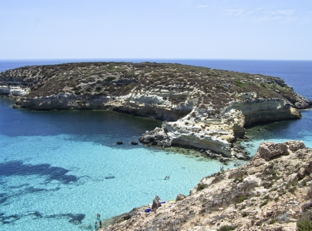 This is the magnificent island of rabbits, in Lampedusa  The water is crystal clear and the sand is white  The rocks are silhouetted against the blue sea and the sky is clear  The depths of this island are a paradise for divers because they are full of co