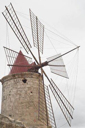 Old windmill on the salines near trapani photo