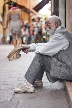 BOLOGNA - JUNE 2012- A homeless old man beggar sitting on the street and asking for help on  May 14, 2011 in BOLOGNA, Italy.