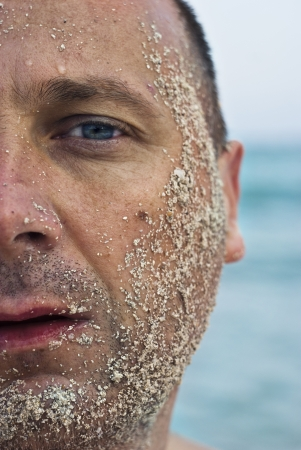 Half face of a handsome man covered with sand photo