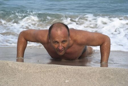 Man doing pushups on the beach.