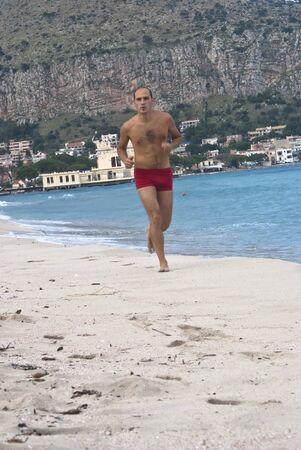mondello: Young Man Running Along Beach at Mondello, Sicily Stock Photo