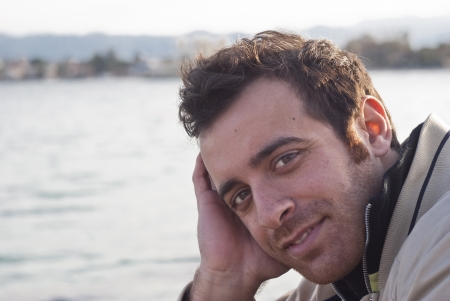 intriguing: Intriguing look of handsome man with sea in background. Stock Photo