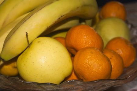 Glass basket full of fresh fruits photo