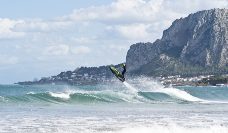 jet skier: man jumps on the jet ski above the water at Mondello. Sicily