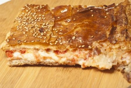 Sicilian rotisserie. piece of rotisserie with mozzarella and tomato sauce on wooden board. photo