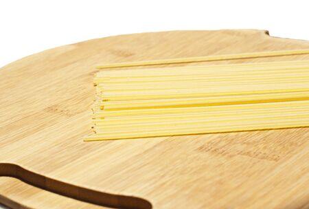 spaghetti pasta on wooden board isolated on white photo