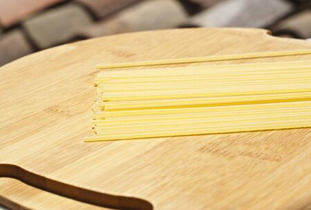 spaghetti pasta on wooden board with roof in the background  photo