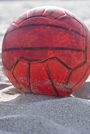 orange soccer ball on beach photo