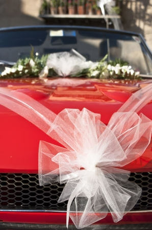 Red wedding car with white ribbon and flowers on the windshield photo