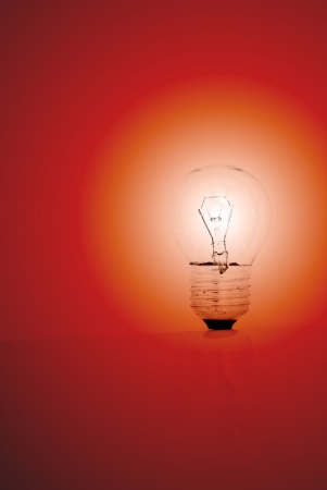A lit light bulb on a red background.