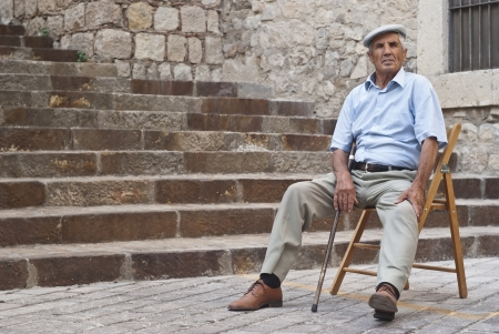 POLIZZI GENEROSA, SICILY-AUGUST 19: old Sicilian man, sitting waiting for the parade at the International Festival of hazelnuts: August 19, 2012 in Polizzi Generosa,Sicily, Italy Editorial