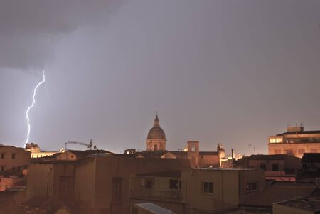 lightning over urban houses in Palemo, Sicily, Italy photo