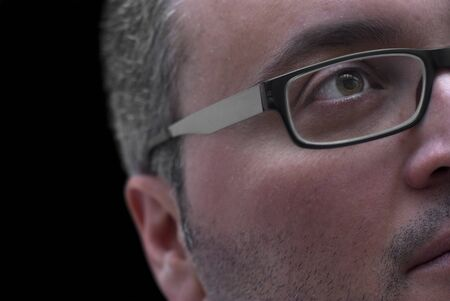Close up portrait of man with glasses on black background photo