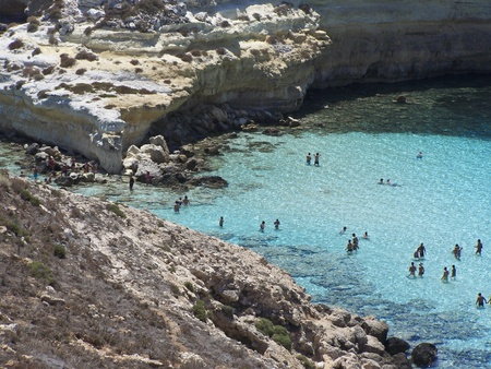 This is the magnificent island of rabbits, in Lampedusa. The water is crystal clear and the sand is white. The rocks are silhouetted against the blue sea and the sky is clear. This area is protected reserves.
