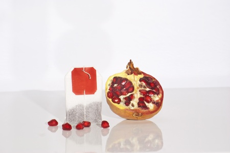 Juicy pomegranate and tea bag on white background Stock Photo - 16986046