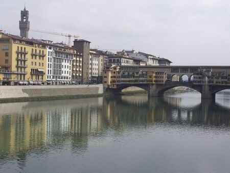 sightseeng: The Ponte Vecchio is a Medieval bridge over the Arno River at evening. Florence, Tuscany, Italy.
