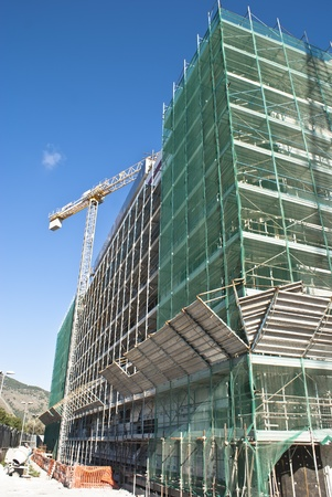 High-rise building construction site with cranes against blue sky photo