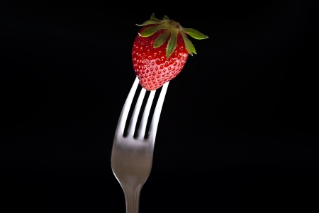fresh strawberry on fork isolated on black background photo
