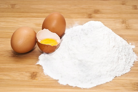 Eggs and flour. preparation of pasta on wooden table photo
