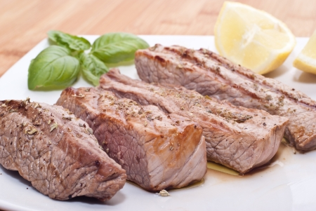 Grilled beef sliced with basil and lemons photo