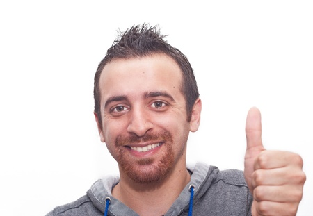 Portrait Of A Happy Young Man Showing Thumb Up Sign Isolated On White Background photo