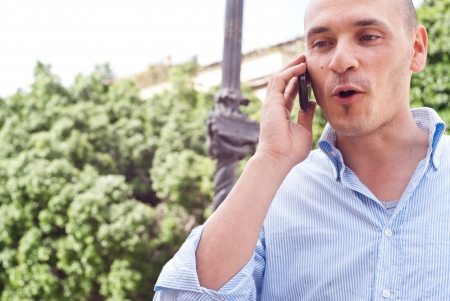Portrait of a handsome businessman talking on cellphone outdoors photo