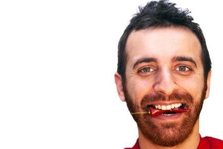 Young caucasian man with a red hot chili pepper in his mouth photo