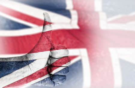 Hand OK sign, wrapped in the flag of the UK photo