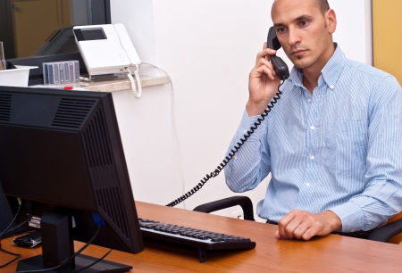 businessman sitting and using phone in office photo
