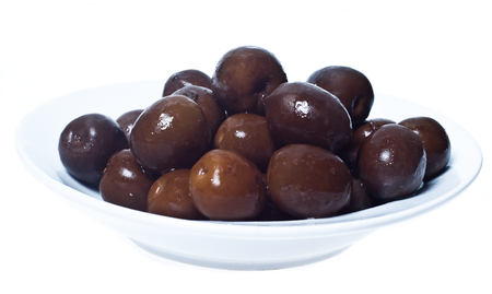 Brown  olives in bowl isolated on white background photo