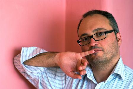 dedo me�ique: Hombre cauc�sico barbudo serio el uso de anteojos me�ique en la boca contra el fondo de color rosa
