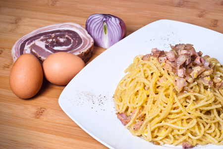 Delicious spaghetti with bacon and egg called alla carbonara on wooden table photo