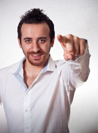 attractive young man pointing a finger towards you photo