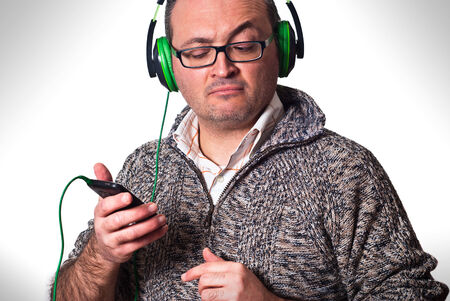 adult man listening to music and looking at cell phone with puzzled look photo