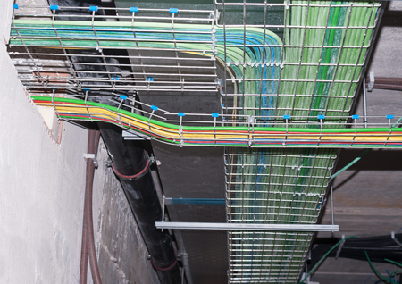 Multicolored pipes and wires silver vents of industrial faclity ceiling horizontal photo