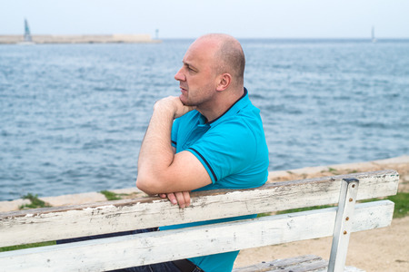 A man sitting on the bench and looking at the sea photo