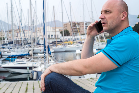 Stylish businessman using his smart phone while sitting near a marine with luxury yachts against a deep blue sky and sea. photo