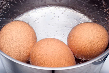 Three eggs boiling in pan of water Stock Photo