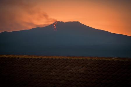erupting: etna volcano erupting at sunset. View from castelmola, near Taormina, Sicily Stock Photo