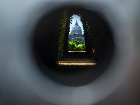 The dome of Saint Peters Basilica seen through the famous keyhole at the the gate of the Priory of the Knights of Malta on Aventino Hill. Rome, Italy, Southern Europe