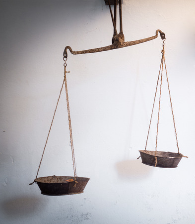 litigate: ancient balance hanging on the old wall in Sicily