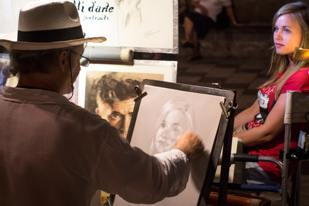 TAORMINA, ITALY - August 8, 2014: Street artist paints a portrait of a beautiful girl in Piazza IX aprile. Shallow depth of field, focus on the portrait.