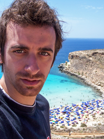 snaps: young tourist snaps a selfie the beach Rabbits Lampedusa. Sicily, Italy
