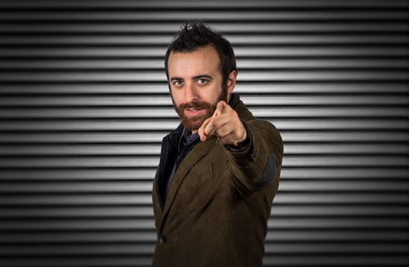 portcullis: Young businessman pointing finger against dark portcullis background.Business concept Stock Photo