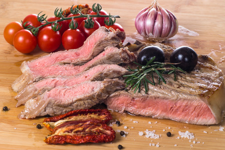Grilled fiorentina steak with spices and vegetables. Closeup