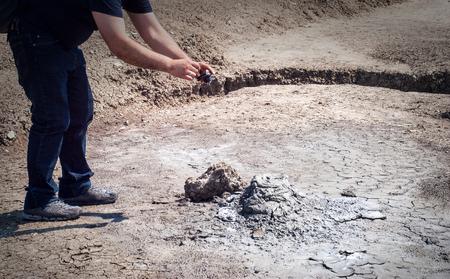 sediments: Man taking photo Mud Volcanoes in Sicily. Nature reserve Macalube di Aragona, Italy