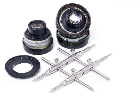 disassembly: Camera lens repair. Camera lens disassembled and spanner wrench tool isolated on white